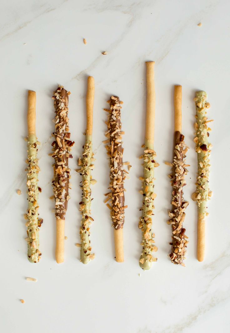 Homemade version of the Japanese Pocky - Crunchy cookie sticks coated with chocolate and garnished with hazelnuts, pecans and coconut flakes