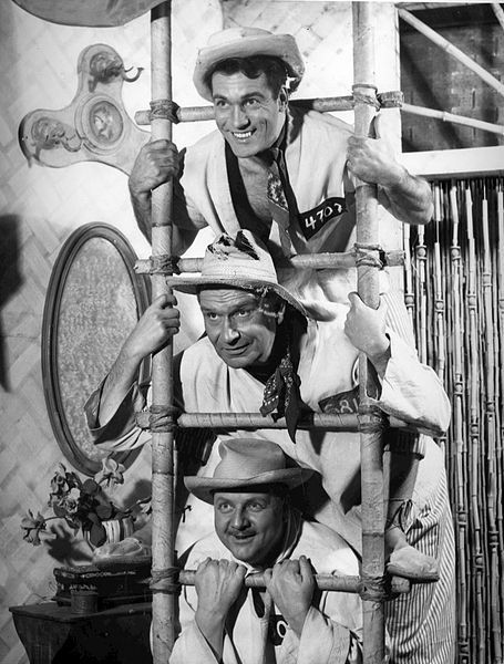 Photo of (from top) Carl Betz (Alfred), Royal Beal and Walter Slezak (Joseph) from the Broadway play My Three Angels, 1954, public domain via Wikimedia Commons.