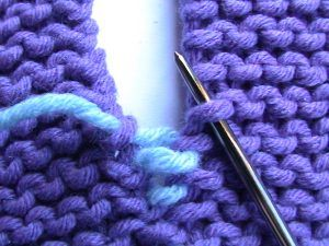Invisible seaming for garter stitch from knitty.com. Click and scroll down to get to the clear instructions.