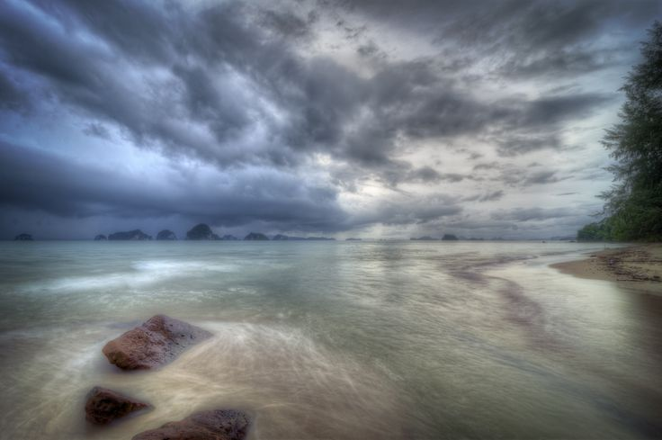 https://flic.kr/p/c8ggtj | Down by the Krabi shore | I came out here hoping i could take in some sunset shots..unfortunately during this time of the year in Thailand, the weather prevents these opportunities in Krabi. That ominous cloud on the left is visual fact of that.   I did manage in a 9-shot HDR, along with some other shots, but that storm quickly came and it came with a brute-like force of wind gusts and rain. So yeah I got my camera a little wet in the process, but given the outcome…