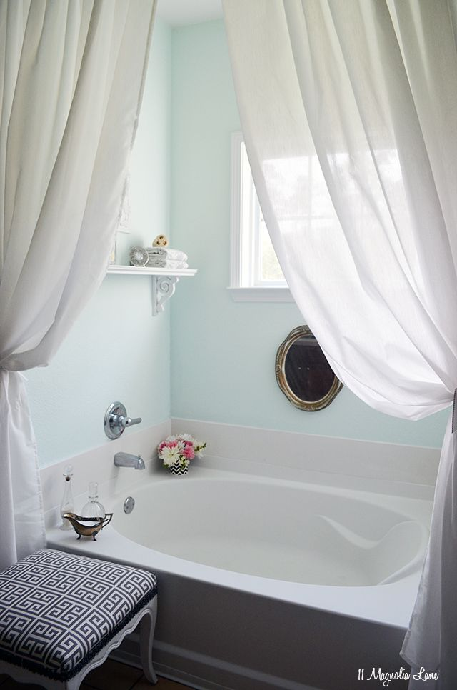 beautiful bath! i love the little things sitting out (flowers, the glass holders + the white curtains really soften it and the old gold mirror ads a bit of chic to it :) also like the aqua colored walls.