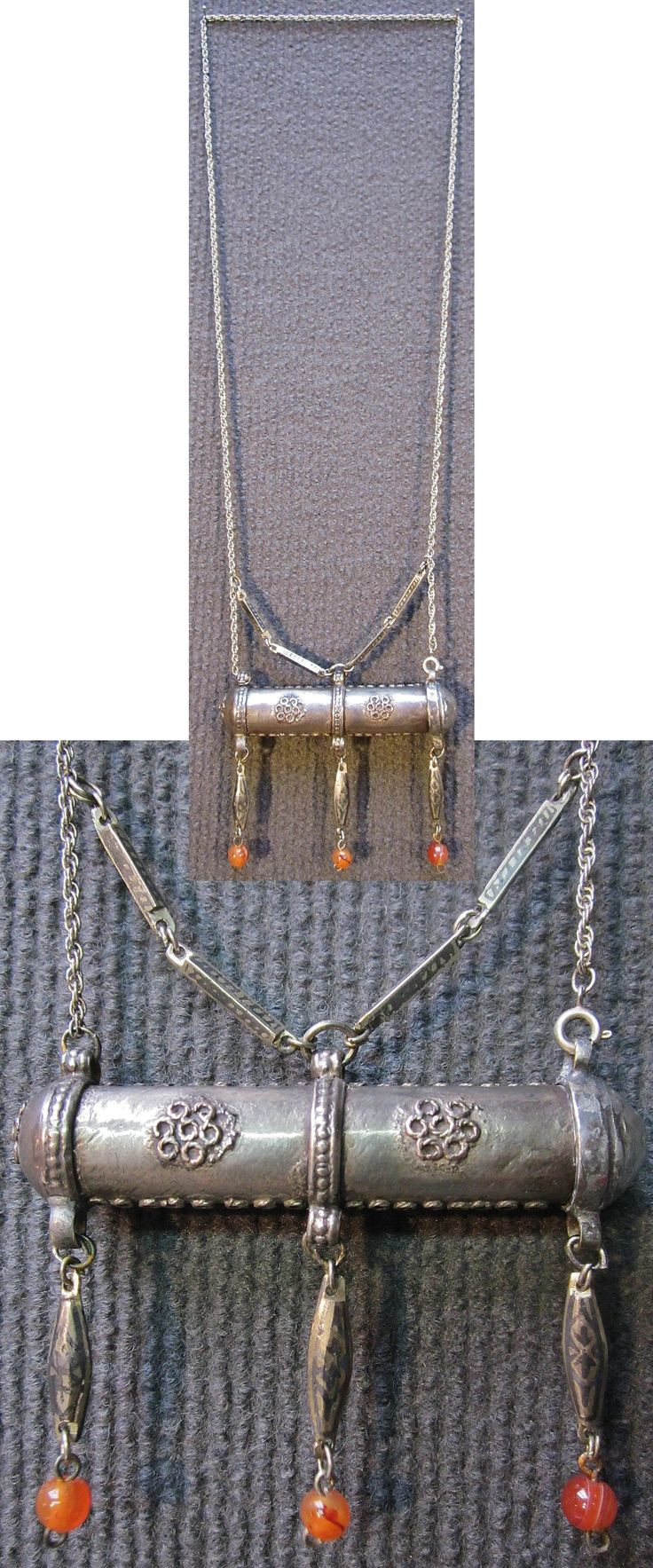 Silver 'muskalık'-necklace (with 'amulet-holder').  From eastern or southeastern Anatolia, possibly Kurdish, ca. 1900.  With niello (on the chains and dangles) and agate (dangles).  The cylinder box is 85 mm wide and has a diameter of 16 mm.  The chains are 66 cm long.   (Inv.nr. müç040 - Kavak Costume Collection - Antwerpen/Belgium).