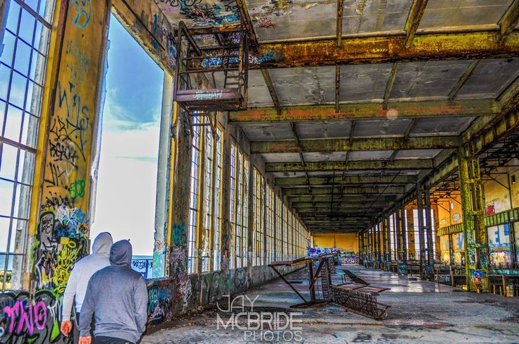 Two men walking through the top level of the South Fremantle Abandoned Power Station - with destruction, damage & graffiti robustly consuming their view, in every direction.