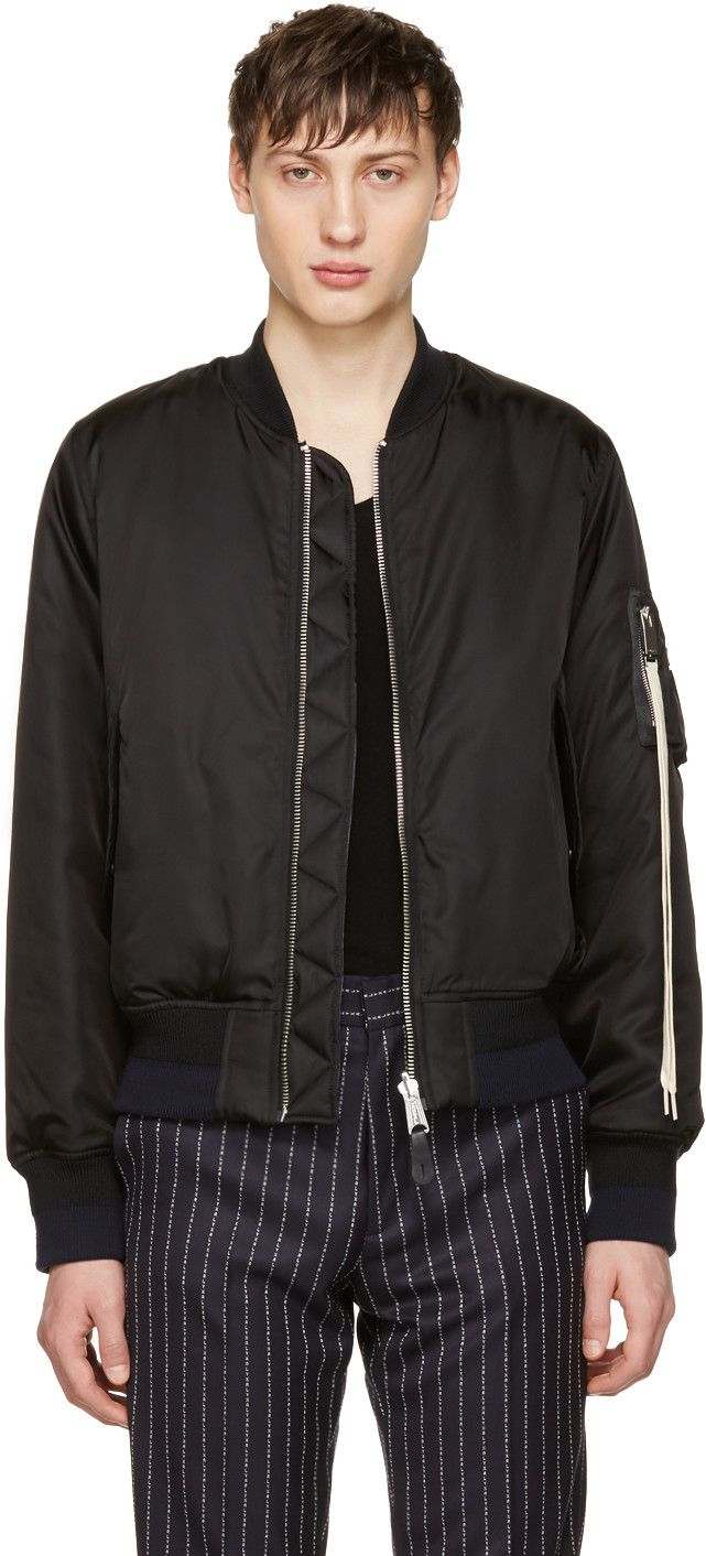 Reversible long sleeve nylon bomber jacket in black. Rib knit stand collar, cuffs, and hem. Zip closure at front. Flap pockets at waist. Utility pockets at upper sleeve featuring detachable oversized shoelace-style pull tab in off-white. Panel at sleeves featuring logo pattern in white. Cuffs and hem colorblocked in navy and black. Reverse in navy featuring welt pockets. Silver-tone hardware. Tonal stitching.   Part of the Alyx x fragment collaboration.