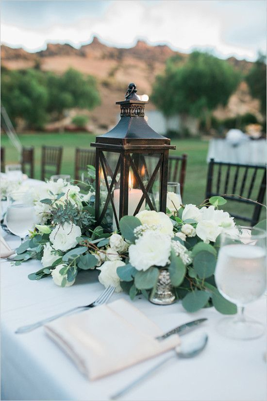 Elegant lantern centerpiece with eucalyptus flower arrangement at an outdoor wedding