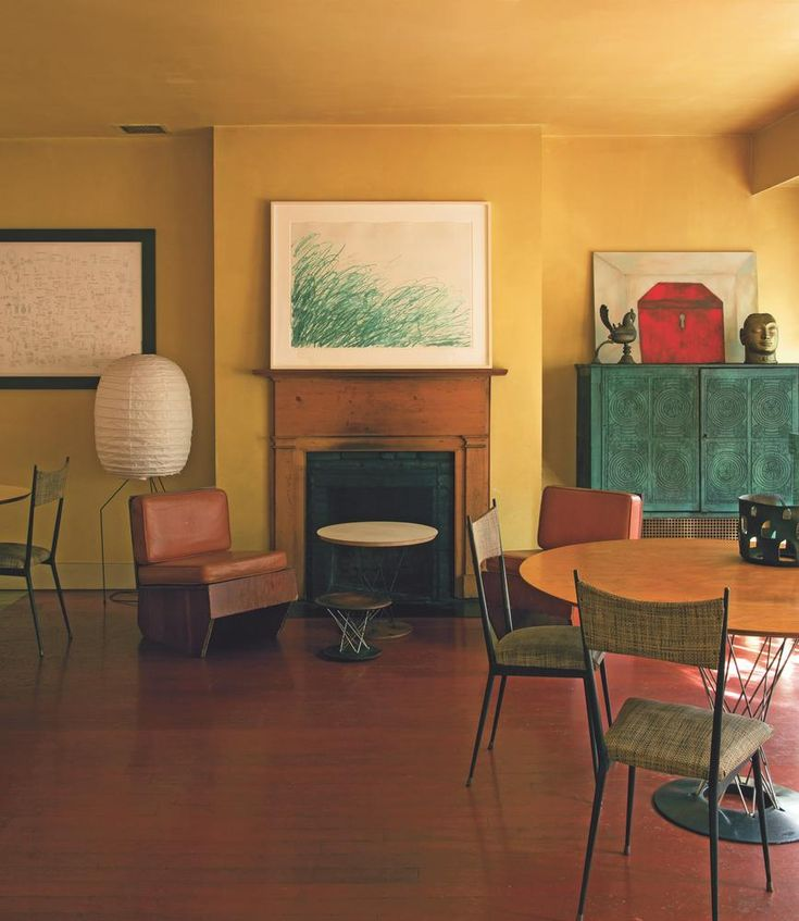 """Italian-born painter Francesco Clemente favors bold earthy hues throughout, a palette inspired by the pigments in his own work. """"He liked the idea of living among his frescoes"""" In his dining room, mustard walls harmonize with a Twombly print, a Basquiat drawing (left) and one of the artist's own paintings (right). Stronger colors, too, can act as surprisingly effective backgrounds for hanging art. """"Petrol blue or chartreuse or acid yellow—those are really big color schemes at the moment."""""""