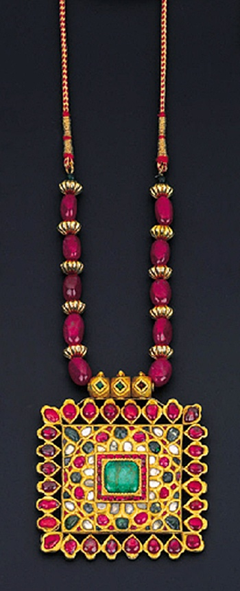 A GEM-SET PENDENT NECKLACE The rectangular plaque centering upon a cabochon emerald within a diamond, emerald and ruby foliate cluster surround to the later ruby bead necklace, the reverse engraved with floral motifs, South Indian, pendant late 19th century, 7.0cm wide