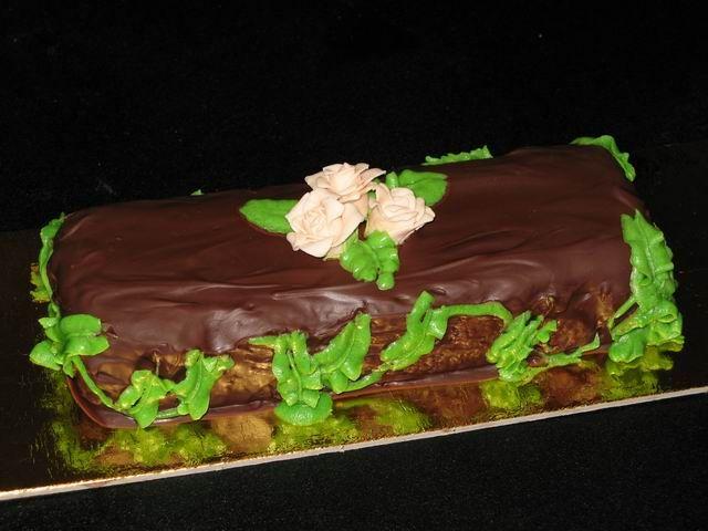 tronchetto di torta al cioccolato  rivestito di glassa di cioccolato, fiori di marshmallow e foglie di crema di burro