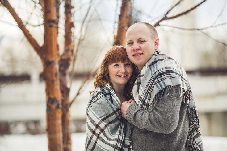 Cute couple cuddling up under a blanket for their winter engagement session in Calgary!