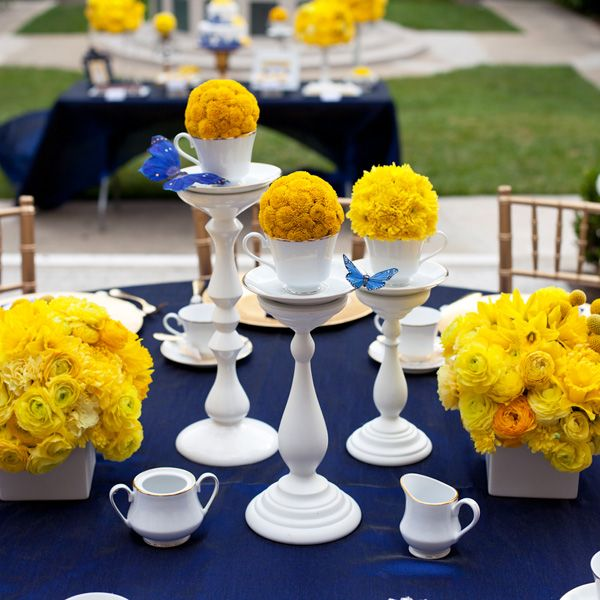 A trio of tea cups were elevated with white pillar candlesticks. yellow floral poms in each tea cup. The tea cup trio was flanked by lush arrangements of yellow china mums, roses, ranunculas, and daffodils displayed in square ceramic vases.    http://blog.hwtm.com/2011/04/royal-wedding-theme-printables-part-1/