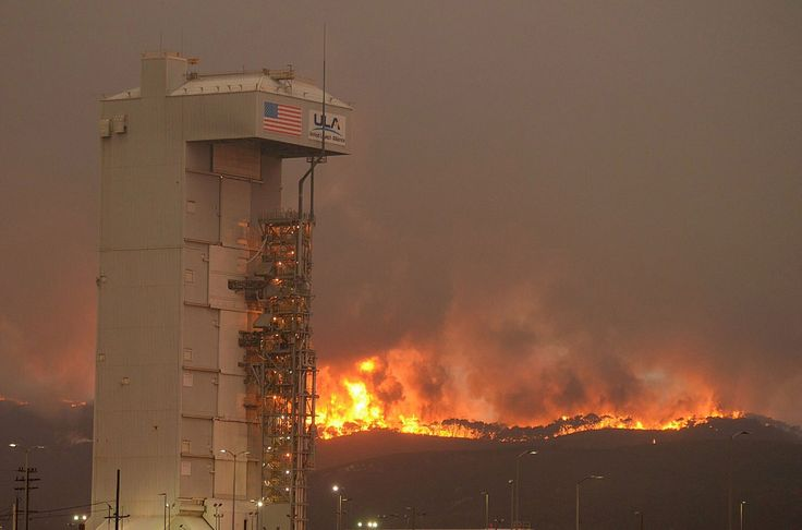 In this Monday, September 19, 2016 photo, a fire burns several miles behind Space Launch Complex-3, housing the Atlas V rocket & WorldView 4 satellite, at Vandenberg Air Force Base, California, Crews are working to surround the wildfire at the central California Air Force base that forced the postponement of a weekend satellite launch. The blaze has expanded to the south as it grew to more than 16 square miles.