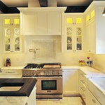 kitchens - white kitchen island butcher block countertop polished nickel faucets hardware white glass-front shaker kitchen cabinets calcutta gold marble countertops pot filler marble mosaic tiles backsplash subway tiles backsplash tapered hammered silver pendant farmhouse sink
