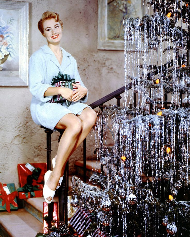 Covering the tree with shiny metallic tinsel and garlands, Shirley Jones 1960