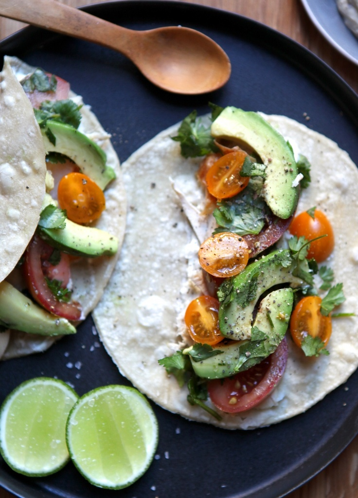 Roast chicken tacos with avocado, tomato, cilantro and spicy yogurt sauce in