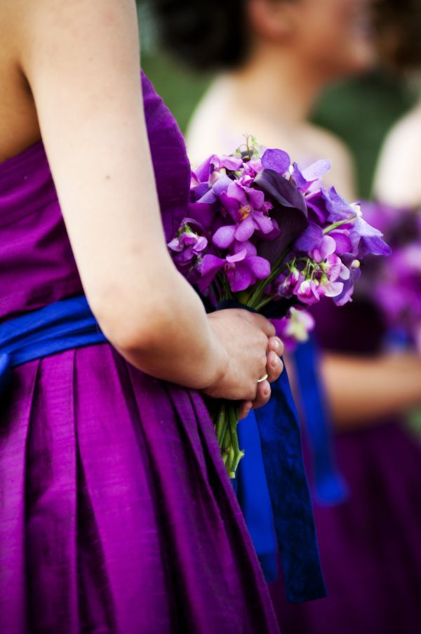 Bright purple bridesmaids dresses with a royal blue ribbon. Perfect for a royal blue and purple themed wedding. Purple and blue bridesmaids dresses are great to match a fall wedding.