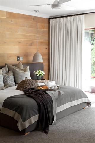In this bedroom, the main wall was clad with flooring planks which adds interesting texture and emphasizes the long, low shapes of the bed and headboard. A deep-pile charcoal carpet was added to bring a sense of luxe and quiet to this room. Simple shapes reduce visual clutter like the bedside tables which conceal phone and tablet chargers. Design: Jeanne Stravino. Issue: July 2014