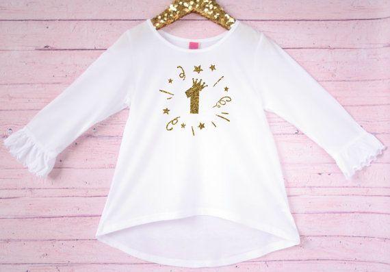 Questo 1 compleanno camicia è perfetta per la tua bambina da indossare per il suo primo compleanno! La camicia ha le maniche 3/4 che sono arruffate alle estremità. Sul retro è un po più lungo del davanti, e va da grande con i leggings!  Tornare alla home page: www.AshlynandEmma.etsy.com  ♥ Questa è la lista per la maglia solo - accessori non inclusi.  ♥ COLORE: BIANCO 3/4 volant manica con lettere di scintillio di ORO scintillante  ♥ MATERIALE: 60% poliestere cotton/40%  ♥ PRO...
