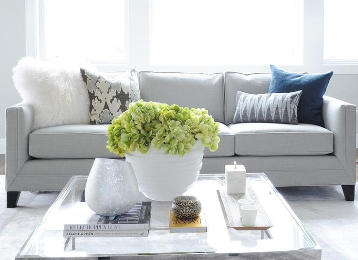 Gorgeous gray linen upholstered sofa topped with assorted gray and blue accent pillows accented by a white sheepskin pillow sits in front of a window facing a polished nickel and glass square coffee table centered on a large gray area rug covering hardwood floors accenting light gray walls.