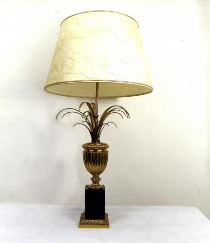 - Brass regency style pineapple leaf table lamp in the style of Maison Charles - This table lamp features large brass leaves mounted on a black stone base - It comes with its original brown light shade with a golden finish on the inside - Two sockets suitable for E27 screw lamps - The lamp is finished with a detailed maize finial