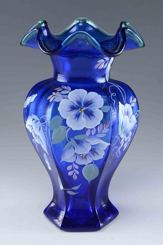 From Fenton Glass company a hexagonal cobalt blue vase with spruce green edge and hand painted morning glories decoration to side that reflects the best of the Fenton tradition in glass making. Hand painted, artist signature to side designed by Robin Spindler. To bottom a a heartfelt message from Bill Fenton celebrating his 75 years.