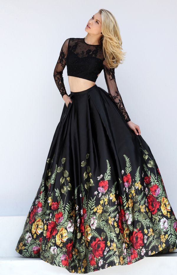 A multi-colored floral print border hemline adorns the ball gown skirt of this Sherri Hill 50599 black dress, completed with a long sleeved crop top. Lace overlays the sweetheart top, creating an illusion jewel neckline and a cutout back. The full-length, box pleated skirt has an inset waistband, concealed side seam pockets and a sweep train.