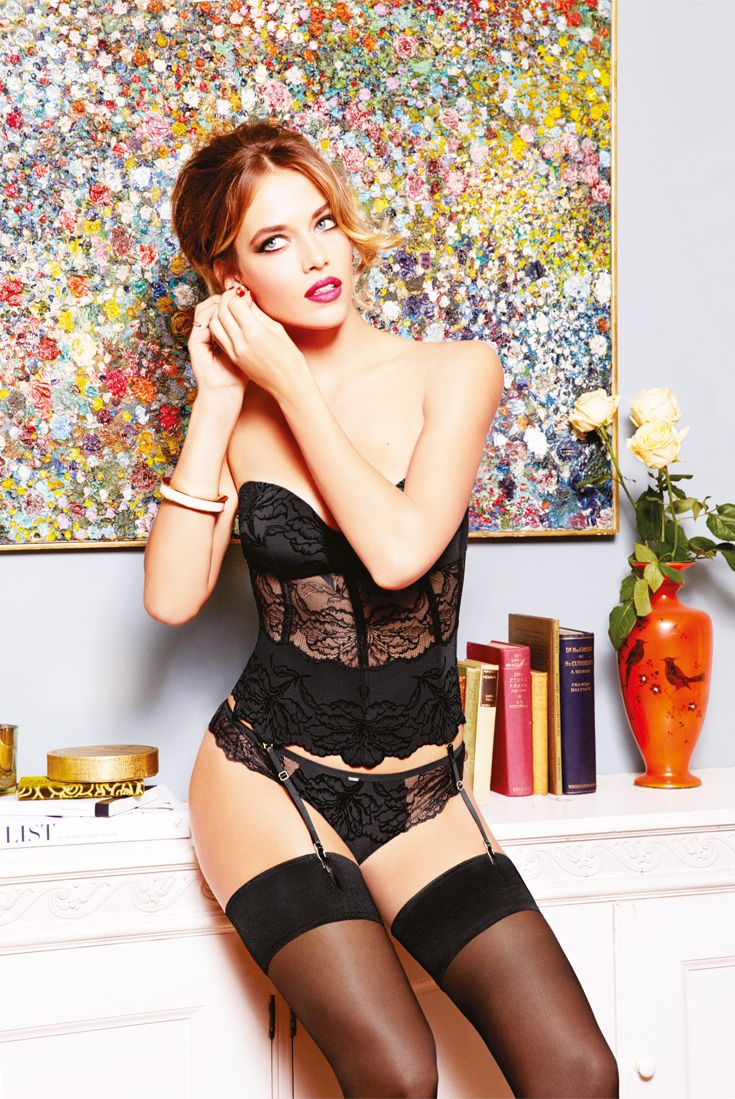 We couldn't do a Christmas seduction look and not do one for New Years! Model Wears Trimph Opulent Essence corsage, String brief and Sheer Stockings. #lingerie