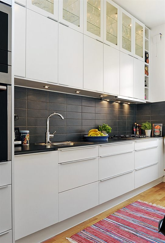 kitchen black counter and back splash white to ceiling cabinets