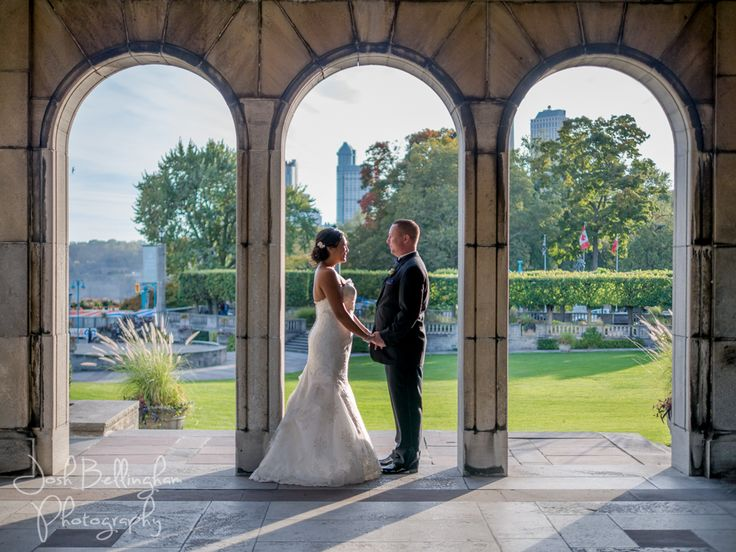 Stunning wedding couple shot with Niagara Falls as the backdrop. Taken at Oakes Garden Theatre in the classical pavilions. Beautiful Bride and Groom under stone archway. #JoshBellinghamPhotography
