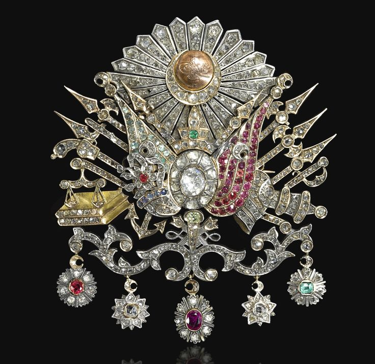 An Ottoman gem-set brooch bearing the tughra of Sultan Abdülhamid II (r.1876-1909), Turkey, circa 1900. Designed with a central diamond between two gem-set flags (one emerald and the other ruby), with miniature copper roundel above with tughra within diamond-set crescent moon emanating rays, fastening pin to reverse, in bespoke velvet-lined box with initial 'A' surmounted by a crown.