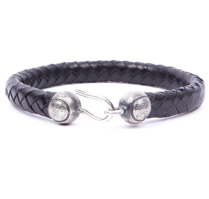 Pulsera Cruzado. Pulsera de cuero trenzado en color negro con insignia en plata de ley envejecida, elaborada totalmente de manera artesanal.