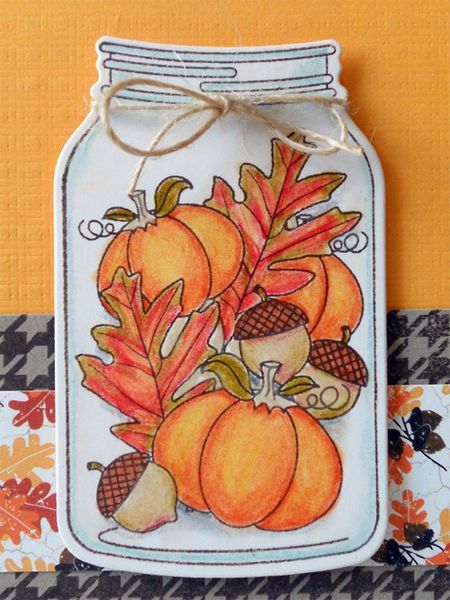 A beautifully colored jar of fall items on a handmade card