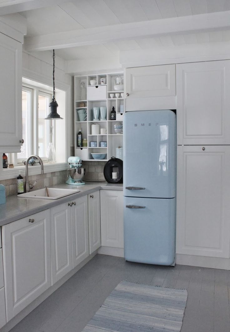 Cute kitchen with retro style fridge. Could use a black and white graphic rug. Something to add some interest and contrast.