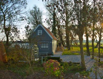 Amsterdam Country Cottage ( Durgerdam) - schattig landelijk huisje op fiets afstand van Amsterdam. Gelegen aan het water met steiger en terras.