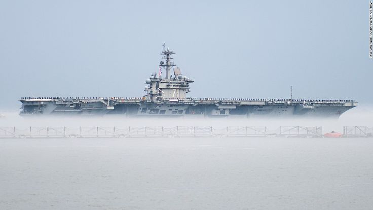 The aircraft carrier USS Theodore Roosevelt departs Naval Station Norfolk, Virginia, The cold water created a fog that made it seem the ship was in a cloud.