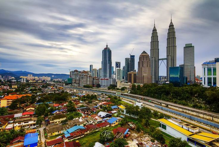 KL contrasts: traditional village Kampung Baru in the shadow of Kuala Lumpur's futuristic skyline. Image by Naim Fadil / CC BY-SA 2.0