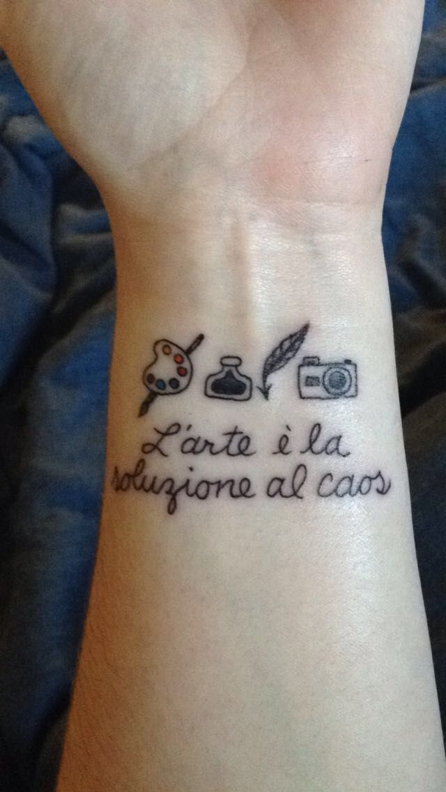 """Paint pallet & brush, ink and quill, and camera with """"Art is the solution to chaos"""" in Italian left wrist tattoo by Nate Mastrud of Addictions Tattoo & Piercing, designed by Maggie Henstorf."""