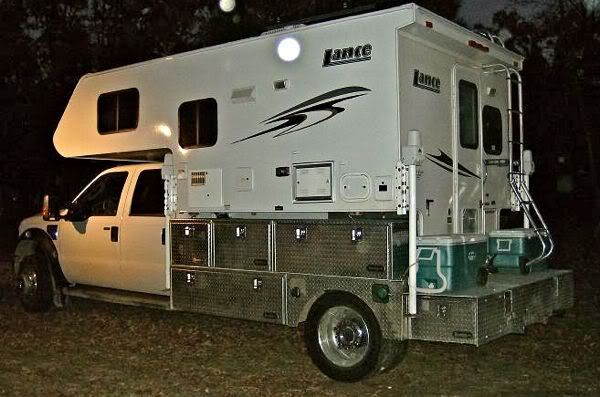 Truck camper on an F-450 flatbed with rear extension for porch and extra storage.