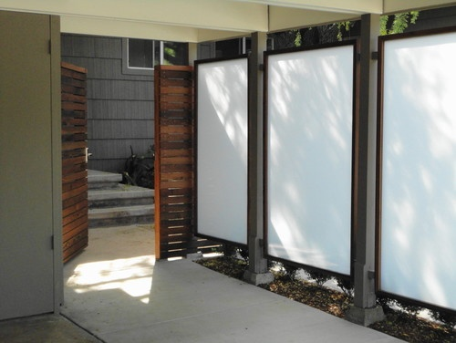 Opaque white glass panels framed in redwood create an illusionary natural lighting source. Here they divide the entrance walk-way and the car-port. The recycled redwood horizontal fence is an architectural feature.