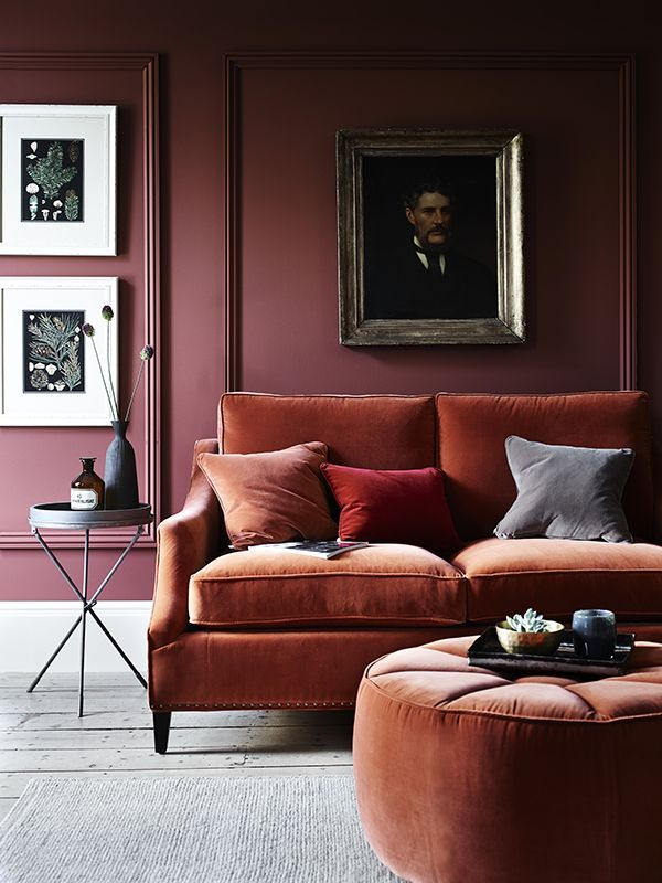 Velvet decorative pillows and sofa in a burgundy painted and paneled room.