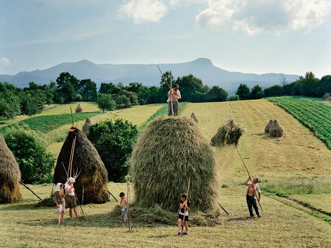 Rena Effendi (Baku, Azerbaijan, 1977): The whole Borca family, from Breb, puts finishing touches on one of the 40 haystacks it makes each summer. Transylvania