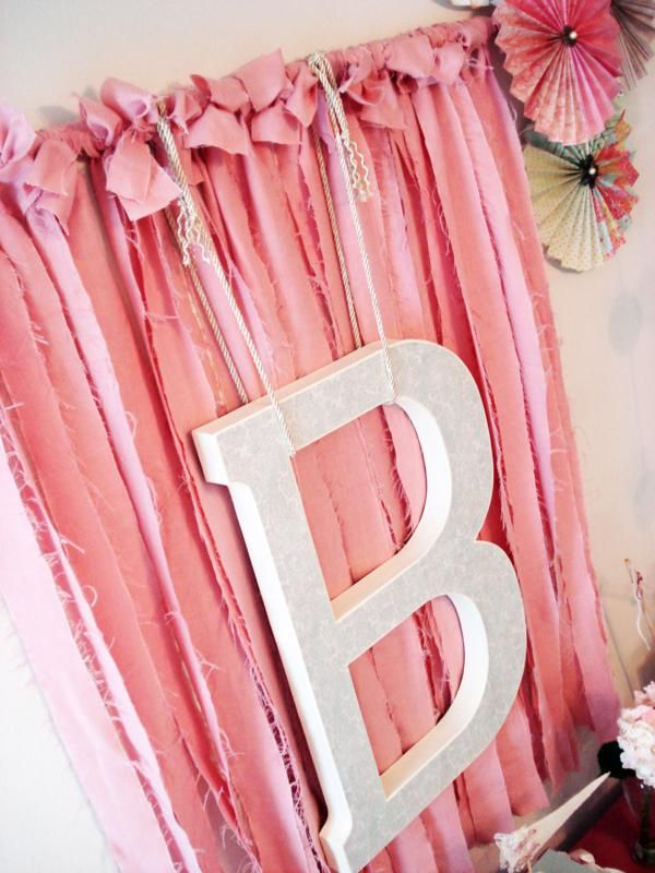 Cute party backdrop idea ribbon and a letter initial for Party backdrop ideas
