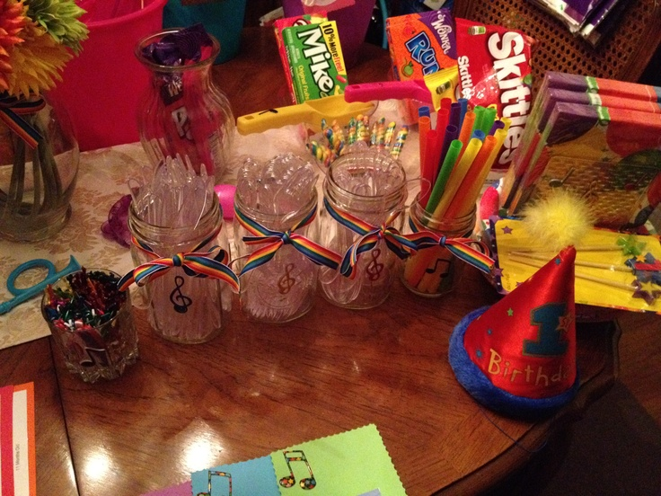 Notekins themed birthday party with music notes on signs, utensil holder mason jars,  candy dishes, and table displays. Also, pictures of each month from birth to 1 year.
