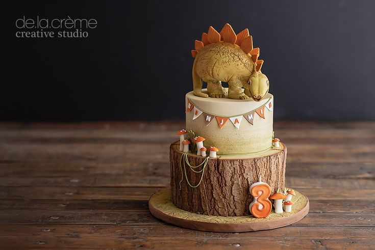 """For the birthday boy who loves dinosaurs, we created a fun Stegosaurus cake  for him and his friends to devour. French Vanilla Cake with Hazelnut  Buttercream, Chocolate Cake with White Chocolate Mousse, and don't forget  those magical mushrooms—I taste-tested one, (you know, for quality control  purposes) and they were delicious!  """"Steg""""the baby dinosaur was amazing to bring to life in the studio. He was  four inches tall, green and covered in scales...not the usual qualities I  look…"""