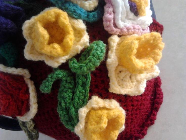 Crochet daffodil flowers on red tea cosy