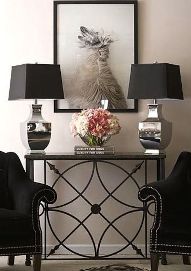 Living Room Console Table Ideas and Tips This beautifully styled wrought iron console table is turned into a living room's focal point with a canine portrait hung above and a pair of black arm chairs with silver nailhead trim.