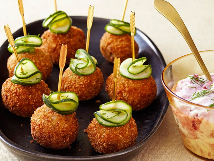 Swedish Meatballs : These bite-size fried meatballs are served with a sliver of pickled cucumber and a dipping sauce made from tangy lingonberry preserves and sour cream.