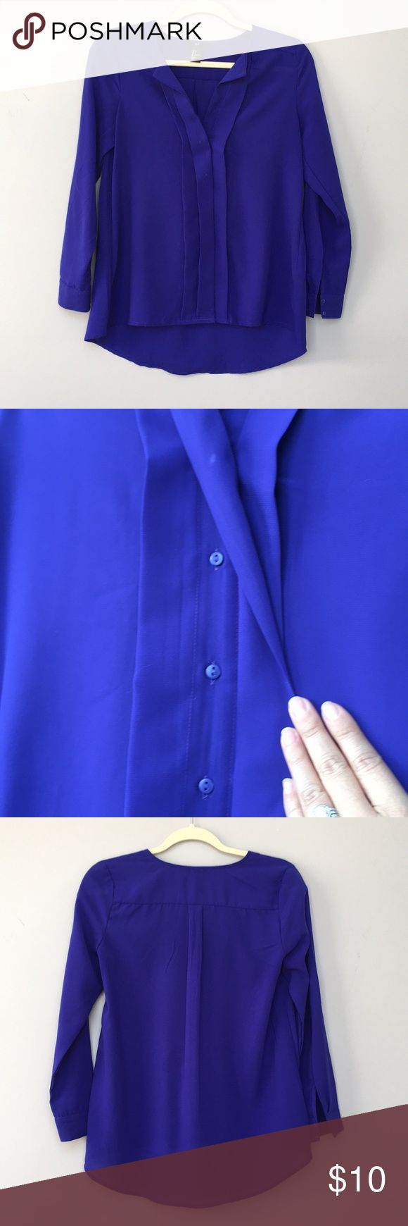 "H&M royal blue blouse Royal blue button down blouse from H&M. Has two buttons on each sleeve. Has ""ruffle"" front that hide Buttons. There look to be button marks in front from ironing, they just look like buttons when wearing. H&M Tops Blouses"