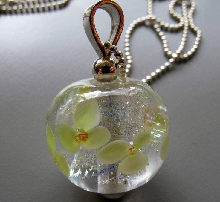crematie as verwerkt in bol van helder glas en bloemen (ook van glas) gemaakt als decoratie