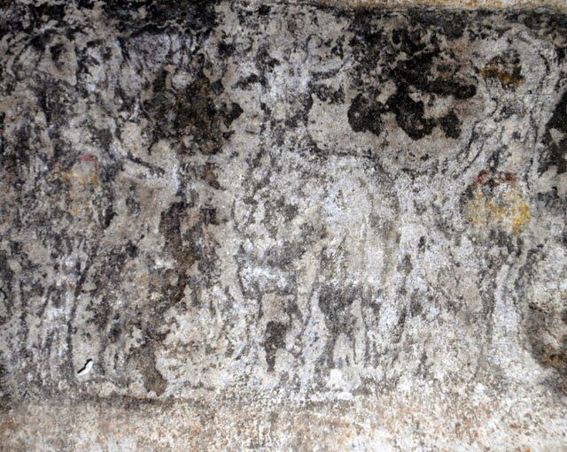 A photo of the fallen architrave above the two karyatides. In the middle can be seen an ox flanked by two figures. At he left a female figure and at the right a male. Behind those figures are moving two winged figures, Nike (?). One of them is moving towards a three-legged stand with a krater on it.