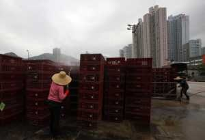 Workers clean empty cages, which were used to transport chickens, after morning trading at a wholesale poultry market in Hong Kong April 8,